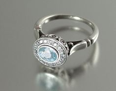 THE SECRET DELIGHT 14k gold Aquamarine engagement ring with White Sapphire halo. $1,140.00, via Etsy.