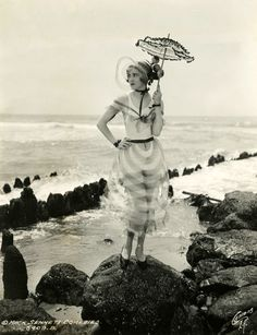 I like how everything is so elaborate in this photo. The pose, the little umbrella, that crazy transparent material...
