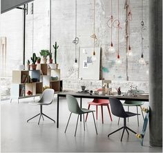 muuto / studio vibes  hanging bulbs, stacking boxes-shelf, greens, concrete walls & flooring, muted colourful chairs, abundance of natural light