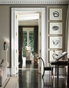 Louis Bustamante. Love the sophisticated elegance, the Greek Key detailing around the moulding, the art work.