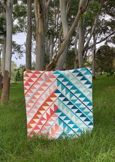 Gather, the latest modern quilt pattern from Suzyquilts.com, looks great in your favorite color palette! The pattern includes a coloring page so you can try out different colors and placements as well as 12 different colorway mockups to spark your creativity. Make this pattern in 4 sizes from Baby to Queen! #trianglequilt #modernquilt #HSTquiltpattern