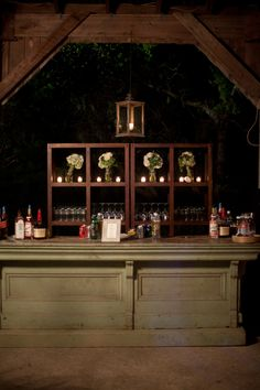 Country store bar at night with heavy wooden bookshelves to display glassware behind it