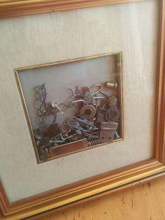 """Metamorfosi. Il quadretto è fatto con minutaglie metalliche recuperate sul fondo di una cassetta per gli attrezzi. Muovendolo gli oggetti cambiano posizione e il """"paesaggio"""" si trasforma."""
