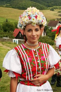 A lovely young lady in traditional dress and headdress in Vlachovo, Slovakia. Vlachovo is a village and municipality in the Rožňava District in the Košice Region of middle-eastern Slovakia. (V)