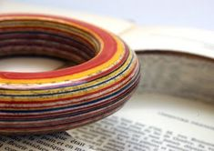 Hundreds of pages from the center of a well-read book, laminated and painted for a one-of-a-kkind ring. Good process for pendants also.