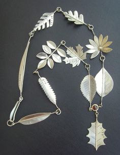 Naomi's leaves necklace made from sterling silver with 9ct gold details and a garnet set above the holly leaf is our Autumn  #DesignoftheWeek  winner!  #jewellerymaking   #Autumn