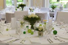 Frühlingshafte Tischdeko mit weißen Blumen und grünen Dekokugeln.
