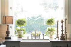 Lamp, topiaries, candlesticks. Would love to have a window like this in my kitchen