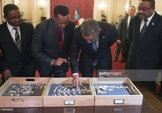 US President Barack Obama (2nd R) touches a bone fragment of 'Lucy', who was estimated to have lived 3,2 million years ago, alongside Ethiopian Prime Minister Hailemariam Desalegn (R) and Zeresenay Alemseged (2nd L), head of the California Academy of Sciences, prior to a State Dinner at the National Palace in Addis Ababa, Ethiopia, on July 27, 2015.  AFP PHOTO / SAUL LOEB