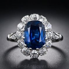 A rich, royal-blue, cushion-cut sapphire, weighing 3.27 carats, radiates from within a halo of bright-white, European-cut diamonds in this original, classic 'Lady Di' ring, finely crafted in platinum.