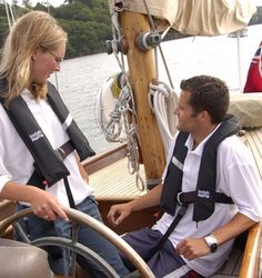 Couple sailing wearing lifejackets