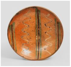 """Berks County, PA Redware Plate with Three-Color Slip Decoration, second half 19th century.  Coggled edge, the interior decorated with three groups of green-and-brown slip stripes interspersed with lines of wavy yellow slip. Rim chips. Some wear to interior. Diameter 8 1/2"""". Crocker Farm March 1, 2014 Stoneware Auction Lot #: 59."""