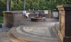 This fire pit patio is adjacent to an outdoor bar area. The seat wall extends from the built-in bar to defines the perimeter of the space and provide seating for both the bar and the fire pit, creating a multi-purpose entertainment zone. Fire Pit Seating, Fire Pit Area, Wall Seating, Patio Seating, Seating Areas, Paver Fire Pit, Fire Pit Backyard, Patio Ideas With Fire Pit, Outdoor Fire Pits