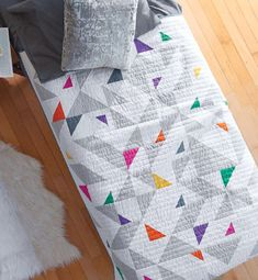The Pop Rocks Quilt Pattern Download designed by Kacia Hosmer is a beautiful modern triangle quilt.