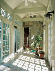 """Seaside Sanctuary, Traditional Home's Cover Story..this """"glass thread"""" links the new home and garage to each other. Marvin doors, stone walls & nautical bulkhead sconces under the vaulted ceiling create an indoor light~filled passageway. Architecture & Interiors by Banks Design Associates, LTD"""