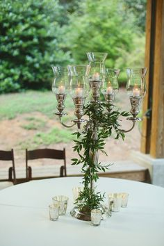 Go #glam at your outdoor wedding with a breathtaking #candelabra centerpiece wrapped in greens! {@jnwfoto}