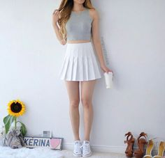 A grey sleeveless crop top, featuring a white tennis skirt and white low top Converse.