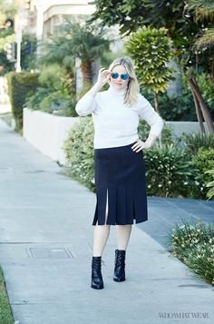 WhoWhatWear Managing Editor Meghan Blalock wears a white turtleneck, car wash pleat skirt, mirrored sunglasses, and lace-up boots