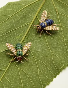 A Pair of Enamel, Diamond, Ruby and Gold Bee Brooches, by Boucheron. Both brooches modelled as a bee, with circular-cut diamond-set wings, to body of green/ blue and black enamel, mounted in 18 karat white and yellow gold.