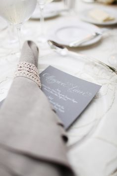 A simplified version of place setting decor - neutral napkin with lace wrap on top of menu