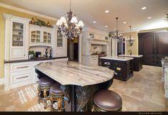 Die Küche ist eine expansive, elegante Ausstattung Raum mit drei vollen Inseln gepaart mit jeweiligen Kronleuchter. Die reich verzierten weißen Schränke und dunkles Holz Insel Strukturen hinzufügen eine elegante Richtung Kontrast.