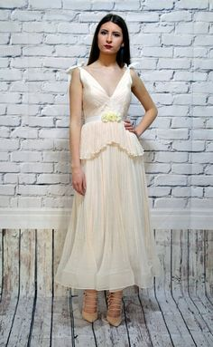 Tea-lenght wedding dress made of draped silk crepe chiffon with grosgrain ribbon bows on the shoulders. This boho wedding dress combines Greek style with the 50th-60th years skirt length and it is suitable both for a wedding dress, bohemian wedding dress or engagement dress. This model has a flower belt sash. Use ZOOM to see al the details.    If you want CUSTOM MADE on your measurements please CONVO me for instructions (no fees added for custom made)        Material: 100% silk. Lining: 100%…
