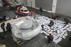 BillionaireMailingList.com - Protestors sort through documents which were left in the house. In the background is a hovercraft and jet-propelled boat