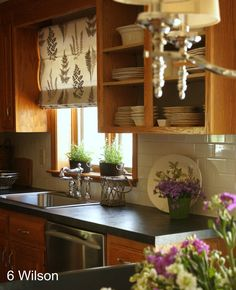 Favourite update for oak cabinets that doesn't involve painting them. Ivory-coloured subway tiles and dark counter top look nice with the cabinets. Splashes of lilac set it off. Super roman blind.