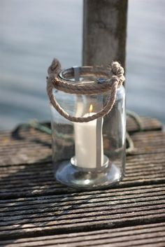 Sleek and stylish Rock Lantern is designed to bring a warm glow of candlelight to your garden, crafted from glass and a nautical inspired rope handle, making it easy to carry.
