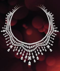 Classic diamond necklace set with fancyshaped and round-cut diamonds. The necklace scallops around the neckline and features diamonds shimmering like raindrops