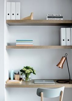 Simple office nook layout. Plain wood shelves for desk and storage.