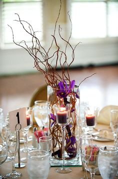 Iris is inexpensive and in this vase with curly willow it makes a dramatic, if slightly slower centerpiece. Also very affordable at less than 10 dollars per centerpiece