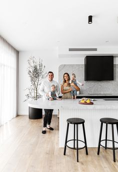 Black, white and grey marble kitchen in modern new build home in Sydney with curved island bench, olive tree in black pot, black island stools. #modernkitchen #monochromekitchen #modernbuild #modernhome #contemporaryhome #monochromehome #homebeautiful