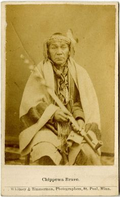 Photograph (black and white); carte-de-visite, portrait of a Chippewa man, seated wearing a cloth shirt, leggings, a blanket, a neck tie, a beaded pouch around his neck, and a cloth headband with a feather in it; he is holding a pipe; Minnesota, United States of America  Albumen print