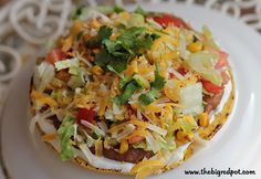 4 point Weight Watchers Tostada  1/2 cup fat free refried beans  1/4 cup salsa  1/2 cup frozen corn  2 tablespoons diced onion  1 tsp butter or olive oil  1/4 tsp cumin  4 tablespoons sour cream   1 cup shredded lettuce  1 tomato, chopped  1 green onion, cut up  8 tablespoons reduced fat cheese (2% variety)