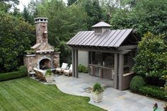 What a great spot to gather in your backyard! The uniquely-shaped concrete paver #patio provides an open spot for guests to sit by the full stone fireplace, and the metal roof covering the cooking area means protection for the sink, fridge, and cabinetry plus a shady spot to grill. We design outdoor kitchens for MN homes. http://www.aldmn.com