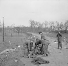 British and German medical personnel assist a wounded German during the Rhine crossing, 25 March 1945.