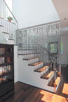 Renaldi-Boyd-Residence-Stairwell - Andrew Magnes's hanging screen composed of aluminum circles and lines, cut with a CNC water jet, separates the entry from the staircase and rear kitchen area.