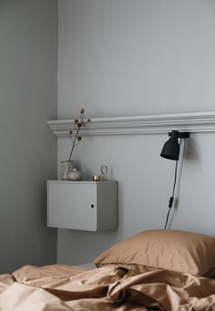 Grey blue bedroom walls and rust coloured bedding | simple black overhead reading lamp | wall mounted bedside table painted the same colour as the wall to blend with the space