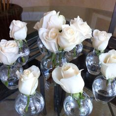 Mini bud vases filled with white roses. Trying ideas for my wedding