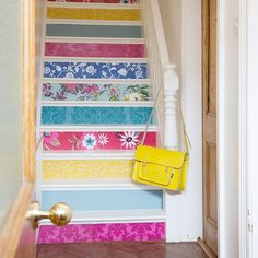 This wooden staircase has been given a colourful makeover using a mix-and-match pattern of funky retro wallpaper swatches on the stair risers.