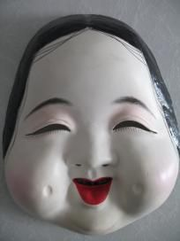 Okame Japanese Mask. Okame is a popular figure in Kyogen, a traditional comic theatre. She is usually see as a pair with Hyottoko. The pair are seen in summer festivals. Okame is the goddess of mirth. She's fun & happy.
