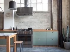 Basis Linoleum in the colour 'Olive' with handles and edges in natural oak. Countertop in natural oak.