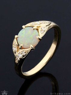 Vintage Leaf Engagement Ring with an opal center stone! Leaves emerge from the band to embrace the prong set center stone. The leaves are set with brilliant diamonds or gemstones. A light engagement ring with lovely breath and spirit.