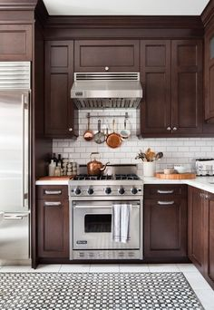 Bistro-style kitchen inspiration: white subway tile backsplash, beautiful marble counter-tops & floor, stainless appliances, with chocolate wood cabinets & copper pans ~ @EpicureanPiranha