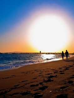 A couple walk along the beach at sunset. Seal Beach, CA Romantic Vacations, Dream Vacations, Seal Beach California, Honeymoon Places, Exotic Beaches, Moon Pictures, Crashing Waves, Great Shots, Life Is Beautiful