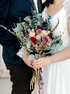 Dried botanical wedding bouquet with pheasant feathers handmade by the bride