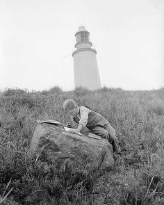 A boy drawing, writing with Cape Bruny lighthouse in the background. Tasmania. May 3, 1950.