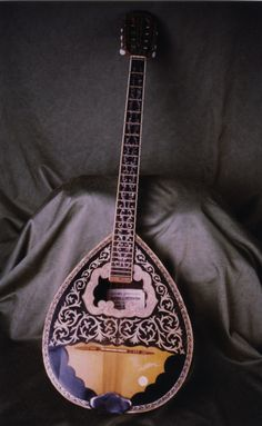 Name LUTE   GREEK LUTE  Classification Chordophone  'Other name' Entry name: Buzuki  'Culture group' Greek  'Culture group place' Greece  Description:  Piriform wooden body, extended neck table and neck inlay with horn & mother-of-pearl 4 double courses of metal strings 27 metal frets head with 8 tuning pegs