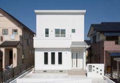 正面から見ると、ホワイトが映えるシンプルなキューブ型。横から見ると、片流れの屋根になっている。門も白で統一して、外観デザインを際立たせている。玄関は少し凹ませ、庇を設けて、使いやすさにもこだわった。白一色の外観が、街に映える